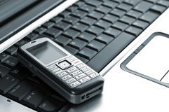 Mobile phone over laptop keyboard Stock Image