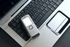 Mobile phone over laptop keyboard Royalty Free Stock Images