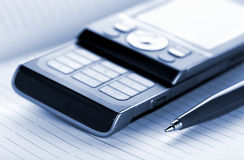 Mobile phone and pen stock photography