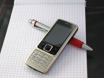 Mobile phone with pen. Mobile phone with pen are on business notepad Royalty Free Stock Images