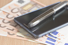 Mobile phone, pen and euro banknotes Stock Photography