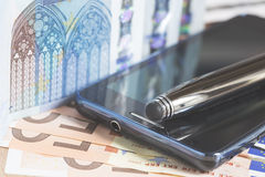 Mobile phone, pen and euro banknotes Royalty Free Stock Photos