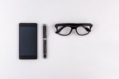 Mobile phone, pen and eyeglasses Royalty Free Stock Image
