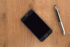 Mobile phone and the pen Stock Photos
