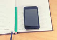 Mobile phone and pencil Stock Photos