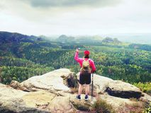 Mobile phone photographer. Tourist on the rocky edge take phone pictures. Hiking in mountains. Enrich life Royalty Free Stock Image