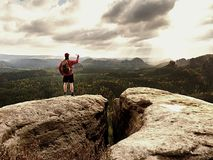 Mobile phone photographer. Tourist on the rocky edge take phone pictures. Hiking in mountains. Enrich life Stock Images