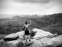 Mobile phone photographer. Tourist on the rocky edge take phone pictures. Hiking in mountains. Enrich life Stock Photo