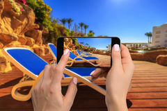 Mobile phone photography of a beach wide view horizontal. Close-up hand holding phone shooting beach Royalty Free Stock Photo