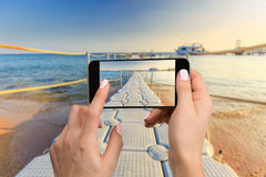 Mobile phone photography of a beach wide view horizontal. Close-up hand holding phone shooting beach Stock Photo