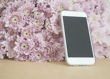 Mobile phone with pink flowers background. Selective focus Stock Images