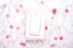 Mobile phone with a pink notebook with pink decorations on a marble background stock image