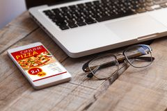 Mobile phone with Pizza shop app in the screen, close to a laptop and an eyeglasses on a wooden table. Stock Photography