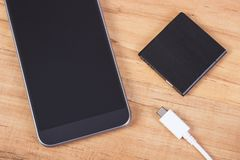 Mobile phone, plug of charger and telephone battery Royalty Free Stock Images
