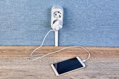 Mobile phone is plugged in socket. Charging  of smartphone with the charger and cable,  plugged into the electrical plug outlet royalty free stock photography