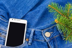 Mobile phone in pocket, twig Christmas tree. White mobile phone in pocket of blue jeans and twig Christmas tree Royalty Free Stock Images