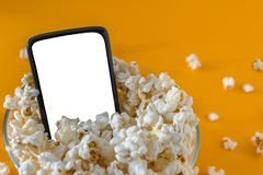 Mobile phone and popcorn in a bowl, on a yellow table, close-up. Technology concept stock photography