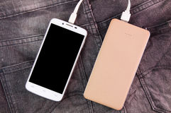 Mobile phone portable battery recharging a smartphone on jeans b Stock Photos