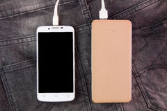 Mobile phone portable battery recharging a smartphone on jeans b Royalty Free Stock Photography