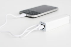 Mobile phone portable battery recharging a smartphone. On white background Stock Image