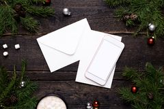 Mobile phone and postcard on a wooden table with a Christmas tree stock photos