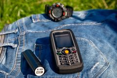 A mobile phone and a power bank on a jeans on background clock. royalty free stock image
