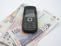 Mobile phone on Rands. A black mobile phone on South African Rands. Image isolated on white studio background Royalty Free Stock Photos