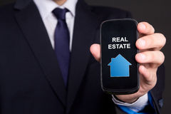 Mobile phone with real estate application in business man hand Royalty Free Stock Photos
