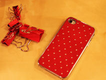 Mobile phone in red bumper with crystals. Cell phone and a clothespin for papers in red color scheme Stock Photography