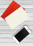 Mobile phone, red envelope and paper on white wooden. Background Royalty Free Stock Photo