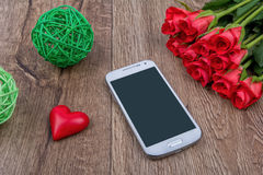 Mobile phone, red heart and roses on a wooden background Royalty Free Stock Images