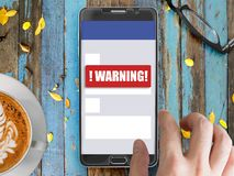 Mobile phone with red warning notification. Smartphone mockup with red warning notification on screen with finger touching Royalty Free Stock Photos