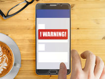 Mobile phone with red warning notification. Smartphone mockup with red warning notification on screen with finger touching Stock Photos