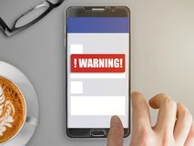 Mobile phone with red warning notification. Smartphone mockup with red warning notification on screen with finger touching Stock Photo