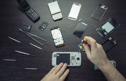 Mobile phone repair, hands closeup. On a wooden table royalty free stock photos