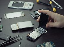 Mobile phone repair, hands closeup. On a wooden table royalty free stock images