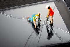 Mobile phone repair service concept. Miniature technician people repairing a cracked smart phone screen. Close up image. Mobile phone repair service concept royalty free stock photography