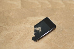 Mobile phone in sand. Stock Images