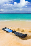 Mobile phone on sand beach Stock Image