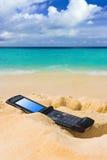 Mobile phone on sand beach Stock Image