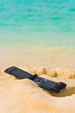 Mobile phone on sand beach Royalty Free Stock Photos