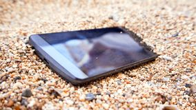 A mobile phone in the sand. A mobile phone with blank black screen sits in the sand at the beach royalty free stock photography