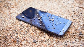 A mobile phone in the sand. A mobile phone with blank black screen sits in the sand at the beach stock image