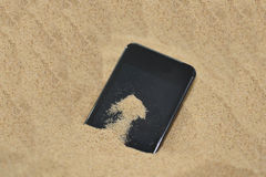 Mobile phone in sand. Royalty Free Stock Photo