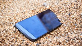 A mobile phone in the sand. A mobile phone with blank black screen sits in the sand at the beach royalty free stock photos