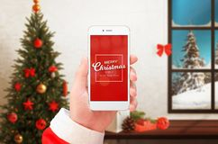 Mobile phone in Santa Claus hand showing Merry Christmas and Happy New Year greeting. Christmas tree and decorations in background Royalty Free Stock Photo