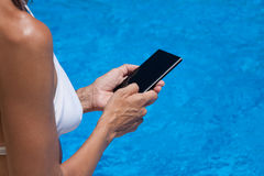 Mobile phone screen in woman hands with water pool behind Stock Photography