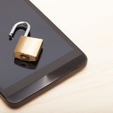 Mobile phone security and data protection concept. Smartphone with a small unlocked lock - close up shot. Mobile phone security and data protection concept Royalty Free Stock Image