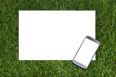Mobile phone and sheet of paper on the grass Stock Photos