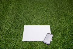 Mobile phone and sheet of paper lying on the grass Royalty Free Stock Photography